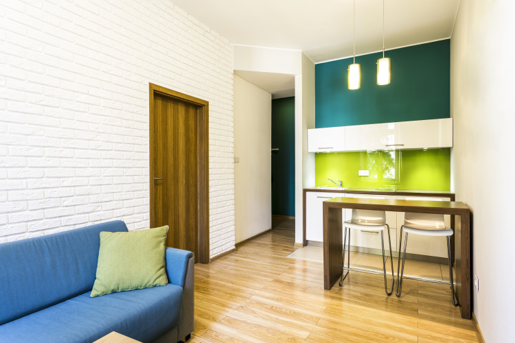 Small living room with brick wall and green kitchenette